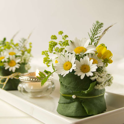 Kleine Gestecke als Tischdecke mit Margeriten umwickelt mit grünen Blättern