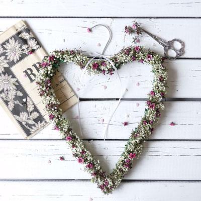 Kranz aus einem Kleiderbügel in Herzform mit Schleierkraut und rosa Wachsblumen