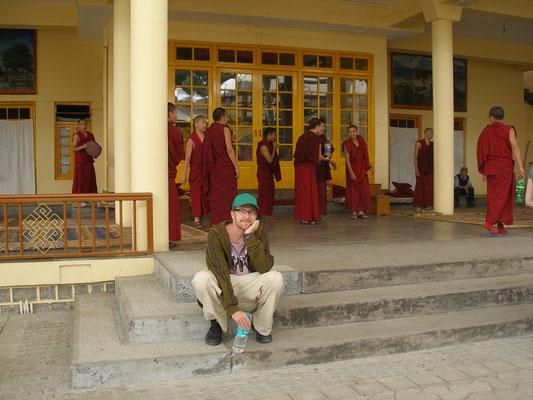 Nicht-Mönche sitzend vor einem Kloster.