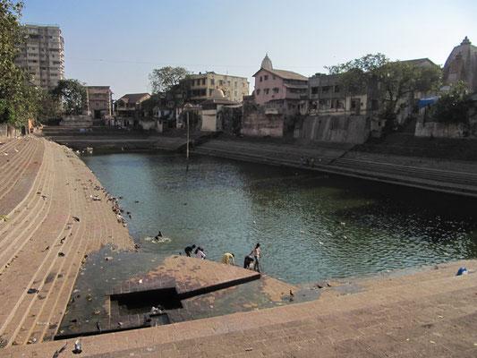 Der Banganga Tank auf dem Malabar Hill. Der Legende zufolge markiert der hölzerne Pfeiler in der Mitte des Wassers den Mittelpunkt der Erde.