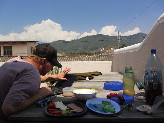 Sebastian skypt während dem Frühstück vor Traumvulkankulisse auf der Terrasse.