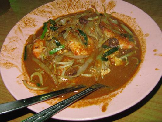 Char Kway Teow auf malayisch. Die gebratenen Nudeln werden in einer Soße serviert.