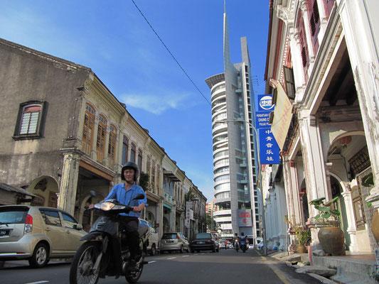 Chinesische Geschäftshäuser mit dem Umno-Turm im Hintergrund.