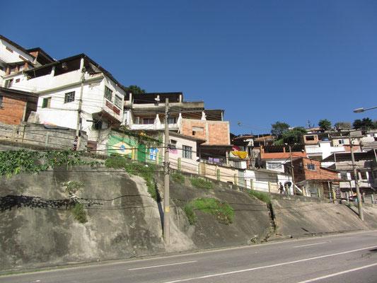 Favela am Straßenrand. Mit Favela werden die besonders in Randlagen der großen Städte Brasiliens liegenden Armenviertel bezeichnet. Es handelt sich um informelle Siedlungen, bei denen die Bewohner nicht über legalen Grundbesitz verfügen.