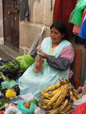 Obst- und Gemüseverkäuferin am Straßenrand.