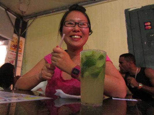 """Glückliche Chihi vor einem Caipirinha. Der ist im Übrigen weitaus billiger als Bier hier. Zur Erklärung: Ein Caipirinha ist ein aus Brasilien stammendes alkoholisches Mischgetränk, ein """"Cocktail"""" aus Cachaça, Limettensaft, Zucker und Eis."""