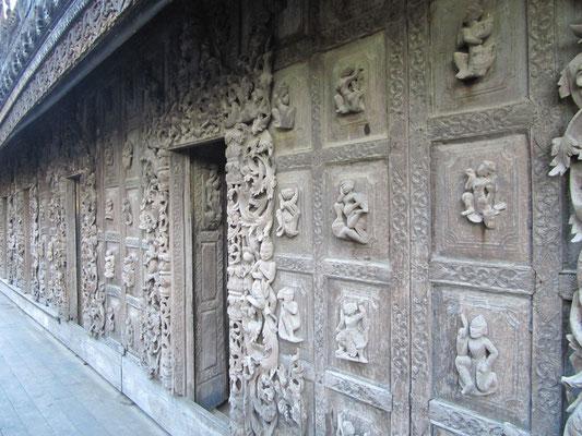Aufwendige Teakholzschnitzereien an der Außenwand des Shwenandaw Kloster.