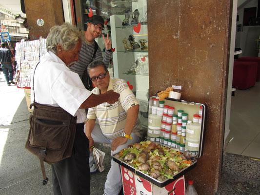 Dieser ältere Herr züchtet in seinem Koffer Schnecken und verkauft ihre Melkerzeugnisse in kleinen Gläschen.