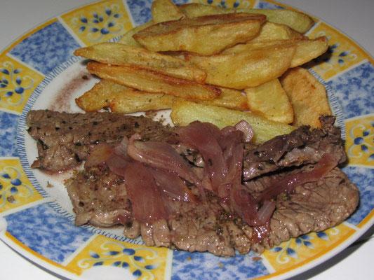 Selbstgemachte Pommes mit Steak in Zwiebel-Rotwein-Soße.