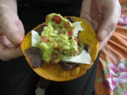 Hausgemachter Taco mit Bohnenpaste, Käse, Jalapenos und Guacamole mit Tomaten.