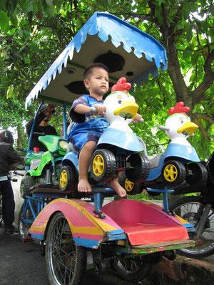 Fahrradbetriebenes Schaukelgeschäft für Kinder.