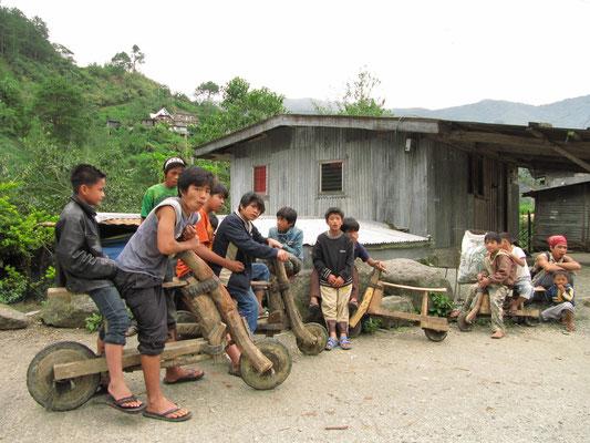 Selbst geschnitzte Roller. Die Serpentinen Banaues bieten Rennsportfreunden ein traumhaftes Erlebnis.
