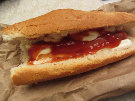 Armes Würstchen mit viel Mayo und Ketchup im Baguette.