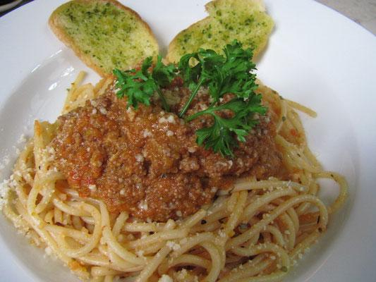 Spaghetti Bolognese mit Knoblauch-Kräuterbaguette.