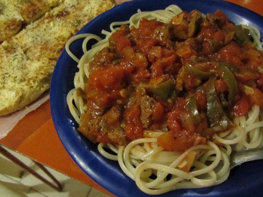 Spaghetti mit Steakstreifen, Paprika und Tomaten, dazu Knoblauchbaguette.