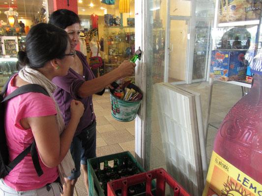 Freundliche Passsantin hilft bei der ungewöhnlichen Flaschenöffnung an der Außenwand des Minisupermarktes.