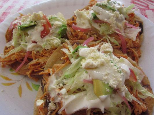 Tacos de Pollo mit einem Haufen Salat.