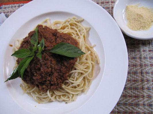 Spaghetti Bolognese aus reinem Rindfleisch mit geriebenem Hartkäse. Garniert mit Thaibasilikumblättern.