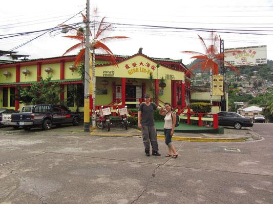 Zwei urbane Wandersleute posieren vor einem chinesichen Restaurant.