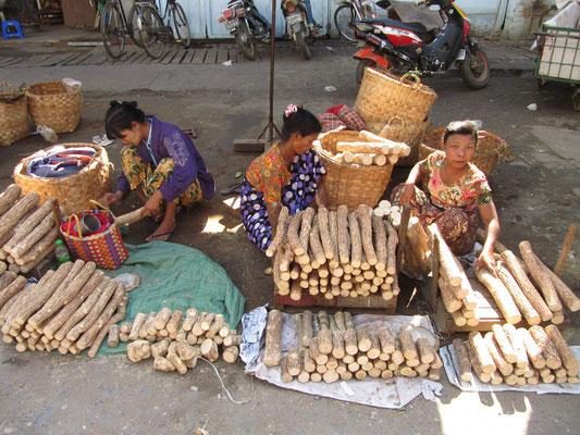 Verkäuferinnen von Stämmen des Indischen Holzapfelbaums.Thanaka ist eine gelblich-weiße Paste aus seiner fein geriebenen Rinde. Sie von Kindern und Frauen in jedem Alter ins Gesicht gestrichen und dient als Make-up mit Kühlfunktion und Sonnenschutz.