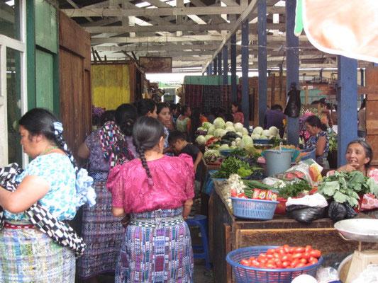 Frauen in ihren tradiotionellen Outfits beim Einkauf auf dem Markt.