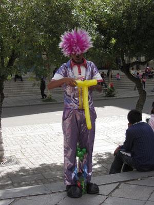 Ein Clown formt lustige Figuren aus Ballonen. (Plaza Murillo)