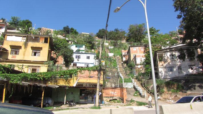 """Favelas werden oft als """"Stadt in der Stadt"""" bezeichnet. Sie sind weitgehend unabhängig von der offiziellen Stadtverwaltung organisiert und werden oft von Drogenbossen kontrolliert. Etwa dreißig Prozent der Einwohner Rio de Janeiros leben in Favelas."""