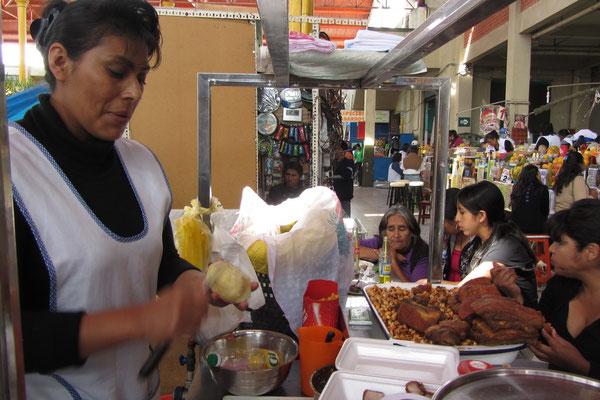 Marktstand mit Frau und knusprig fritiertem Schwein.
