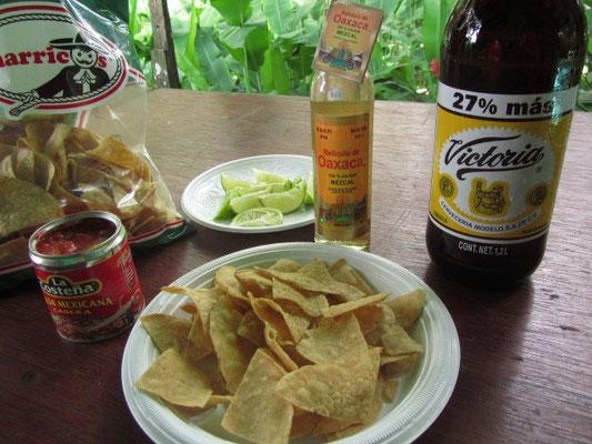 Megapulle Bier, Mezcal und Tortilla-Chips mit Kondimenten.