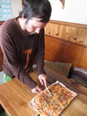 Diego beim Schneiden einer der zahlreichen selbstgemachten Pizzas.