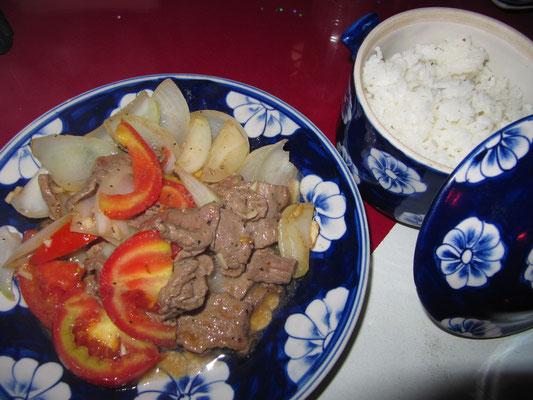Gebratenes Rindfleisch mit Tomaten und Zwiebeln.