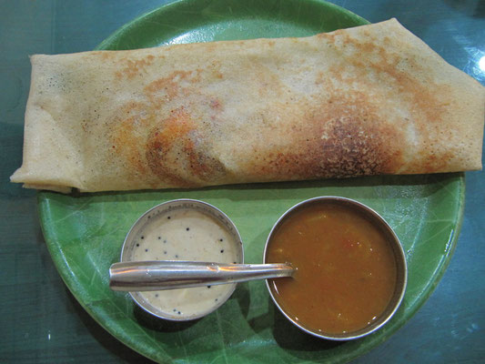 Masala Dosa ist ein knuspriger Reispfannkuchen, gefüllt mit einem würzigen Kartoffelcurry. Dazu gibt's Sambar (einer Soße auf Linsen- und Tamarindenbasis) und Chutney, typischerweise aus Kokosfleisch.