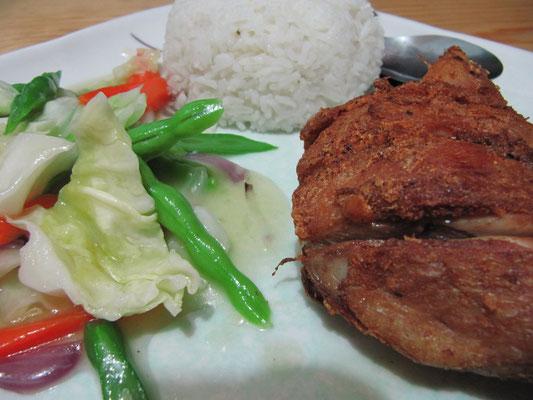 Äußerst stark frittiertes Huhn mit Reis und einer Gemüsebeilage.