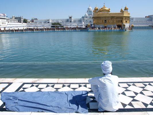 Ein Sikh trocknet seine naße Badekleidung während er meditiert. Im Hintergrund drängelnd die Leute auf der Gurus Brücke um zum Allerheiligsten, dem Hari Mandir Sahib, durch zu kommen. War auch für uns eine reizvolle Aufgabe.