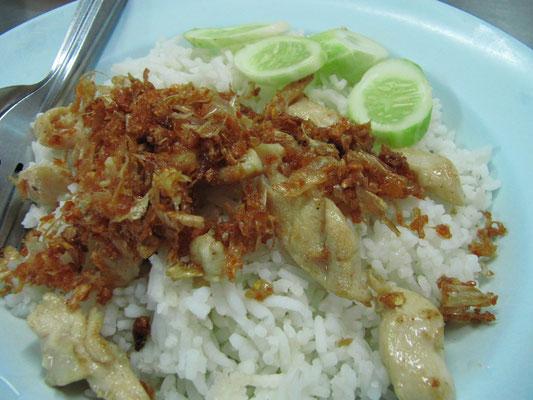 Knoblauch-Pfeffer-Hühnchen auf Reis mit Salatgurkengarnitur.