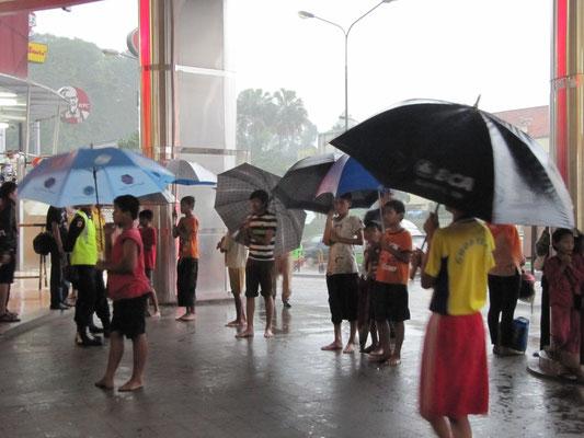 """Kinder warten in der """"Regenstadt"""" täglich und überall mit Schirmen, um bei Bedarf sich ein Trinkgeld verdienen zu können."""