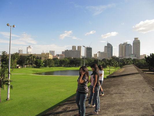 Irre Kombination von Golfplatz, Finanztürmen, jungen Mädels und den alten Stadtmauern Intramuros.