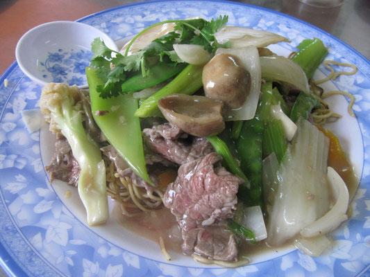 Schwach angebratene Rindfleischstreifen mit Gemüse auf frittiertem Nudelbett.