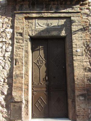 Ein Eingang zur Manzana de los Jesuitas. Symbol des Ordens (hier über der Tür) ist das Monogramm IHS (die ersten drei Buchstaben des Namens Jesus in griechischer Schrift), das oft auch als Iesum Habemus Socium (Wir haben Jesus als Gefährten).