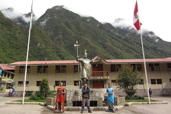 In Aguas Calientes. Ein Toursit posiert unter dem Denkmal des großen Inkakönigs.