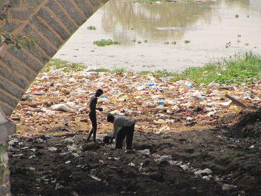 Kinder suchen im Müll nach Verwertbarem.