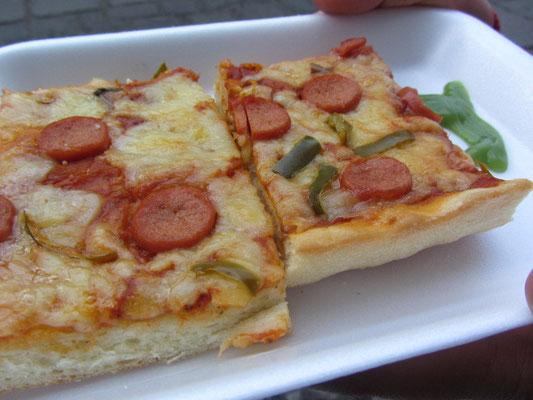 Pizza mit grüner Chillisoße.