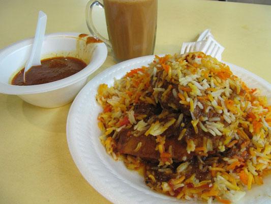 Indisches Briyani mit gegrilltem Hähnchenschenkel, Currysoße und Chai.