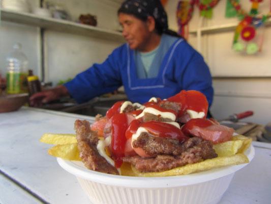 Hamburgerfleisch geschnitten, Wurst geschnitten, das Ganze auf eine üppige Pommesunterlage gebettet und großzügig mit Ketchup und Mayonaise getoppt.