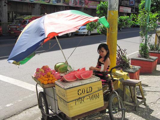 Obstverkäuferin im Einschulungsalter.