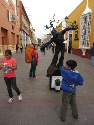 Chihi begutachtet einen Straßenkünstler.