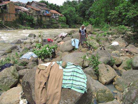 Trockenlegung einiger, vorher im Fluss gewaschener, Kleider.