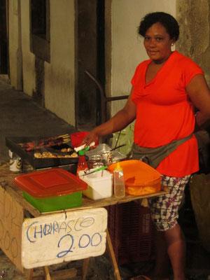 Wurstverkäuferin, die besser grillen als schreiben kann. Das Leben beginnt in Salvador am Abend... und dann wird's feurig wie der Dame ihre Würste und Fleischspieße.