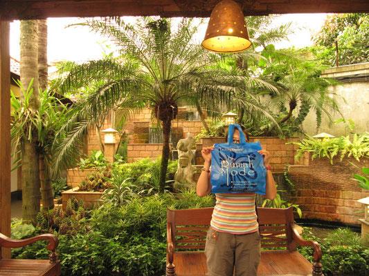 Rumah-Mode-Shopperin verbirgt sich stümperhaft hinter einer Werbetasche.