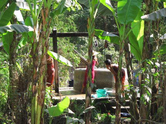 Frauen in waschen sich am Brunnen. (Amarapura)